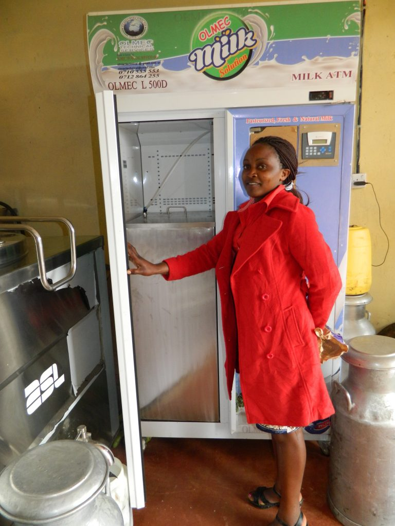"A milk seller at a Milk ""ATM"". The machines have an in-built cooler and use electricity to store and dispense milk. It works like an ATM machine where consumers can key in the amount of milk they want and pay."
