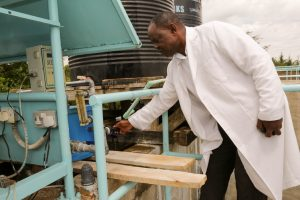 An engineer at NAWASCO checks corrects the amount of coagulant in processing the raw water entering the treatment plant