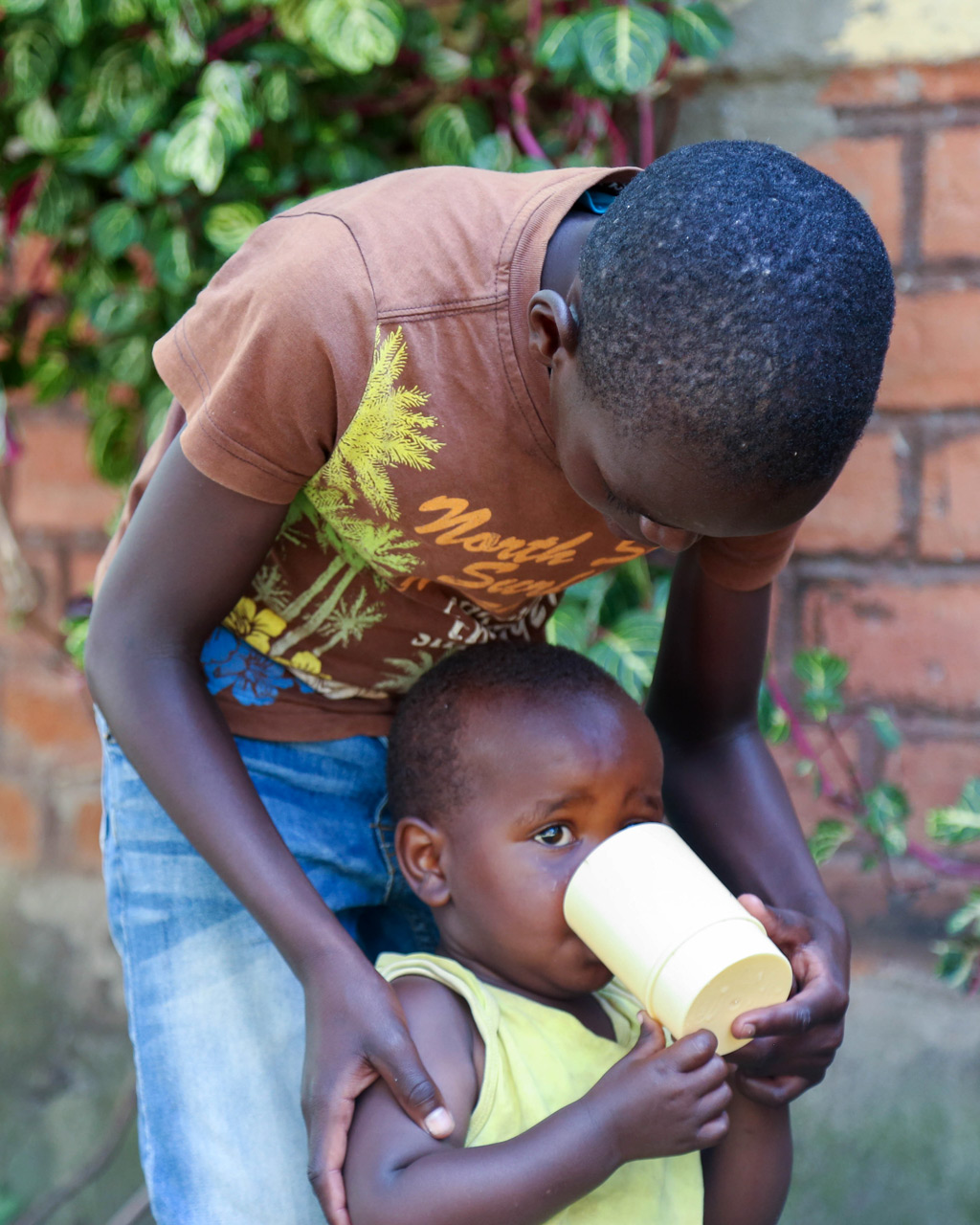 A child drinks safe clean water from a cup | Market Systems Development